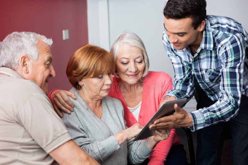 Professeur Assisting Senior Students en utilisant la Tablette de Digital photos stock