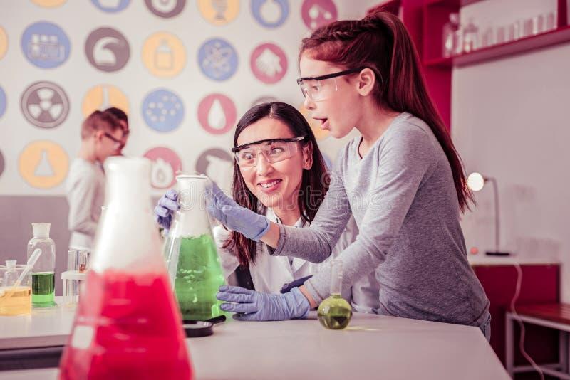 professeur aux yeux ouverts aidant sa salle de gingembre avec le tube géant photographie stock libre de droits