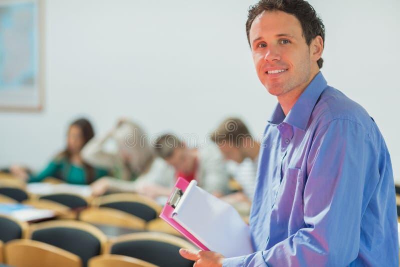 Professeur avec de jeunes étudiants universitaires dans la salle de classe images libres de droits