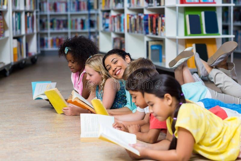 Professeur avec des enfants se couchant tandis que livres de lecture photos stock