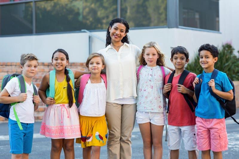 Professeur avec des enfants tenant l'école extérieure images stock