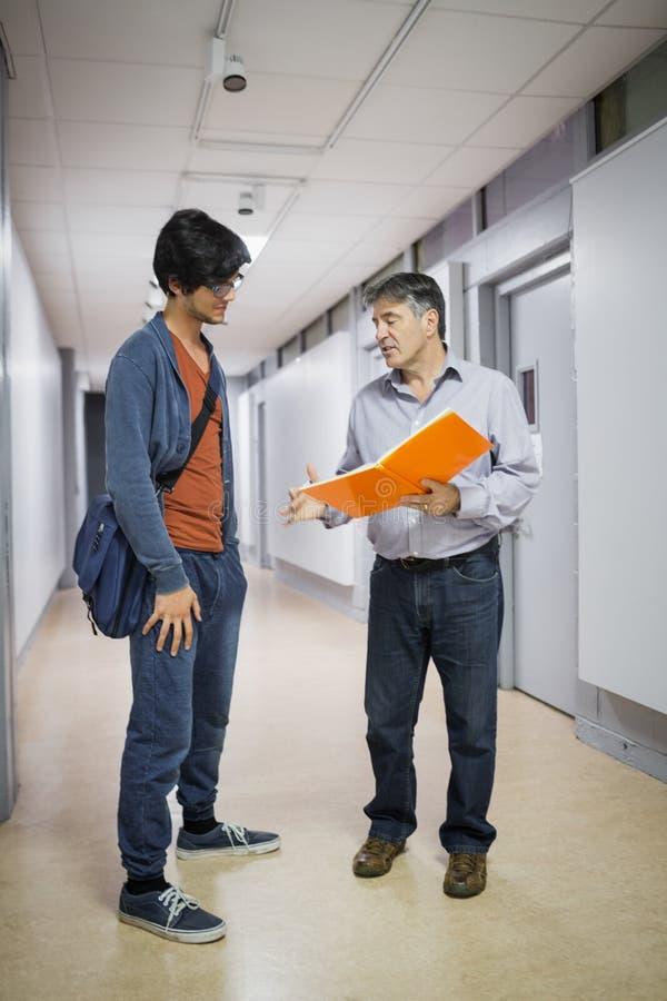 Professeur avec le carnet parlant à un étudiant images stock