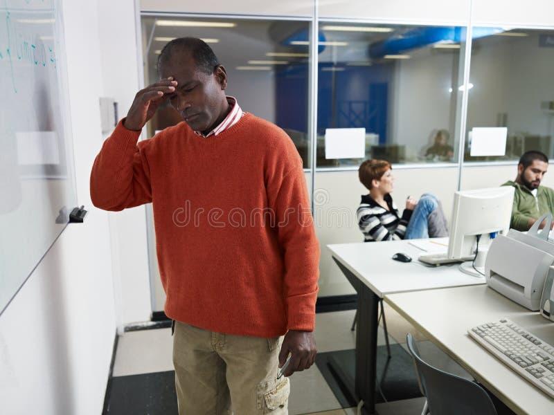 Professeur avec le mal de tête dans le laboratoire d'ordinateur images libres de droits
