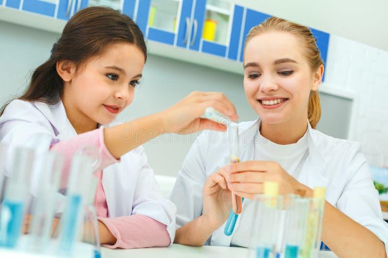 Professeur avec le petit enfant dans l'aide de laboratoire d'école image stock