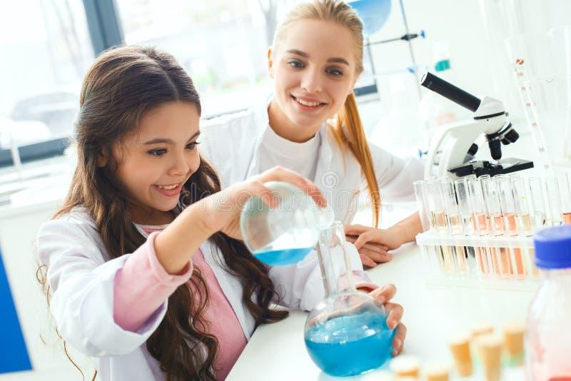 Professeur avec le petit enfant dans le laboratoire d'école faisant l'expérience photographie stock