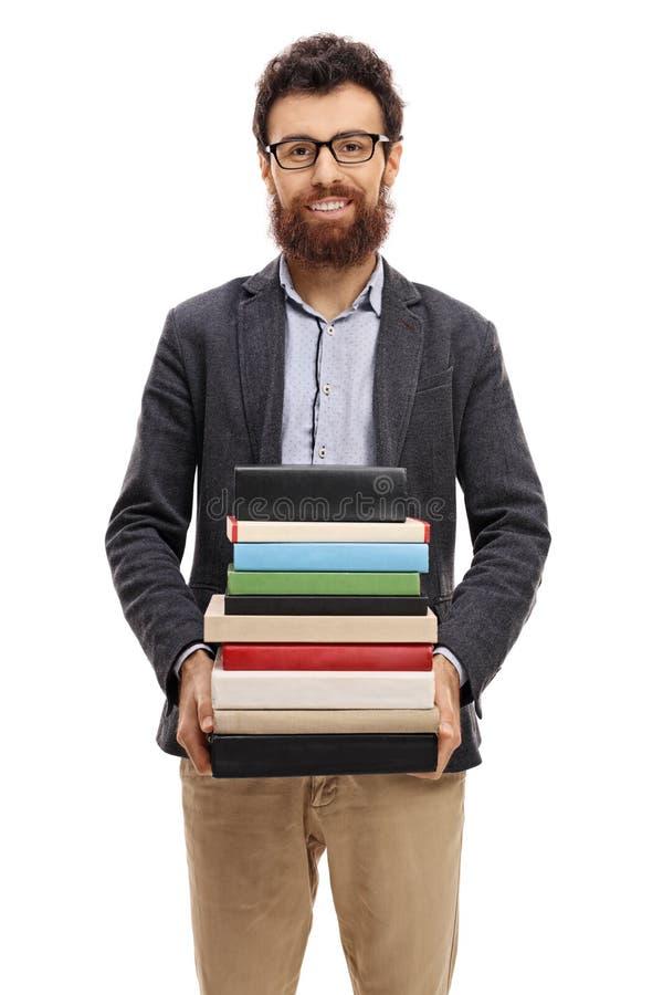 Professeur avec une pile de livres regardant l'appareil-photo images stock