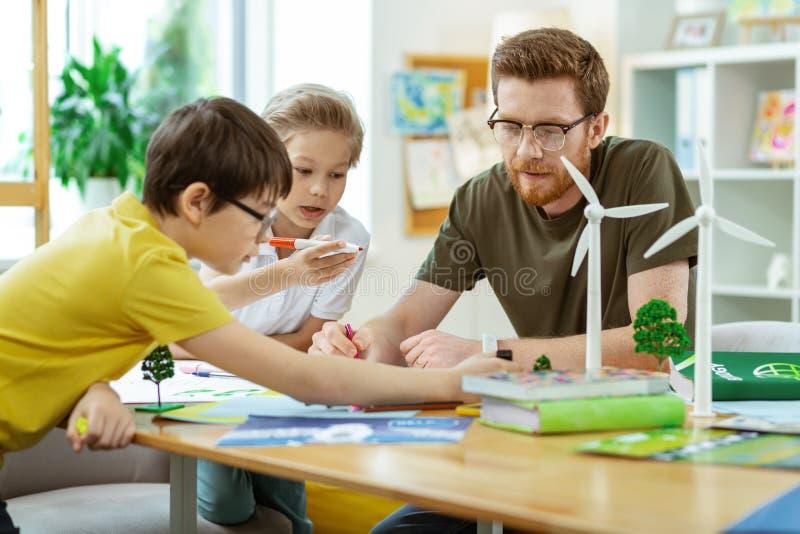 Professeur barbu concentré passant le temps avec ses élèves curieux image stock