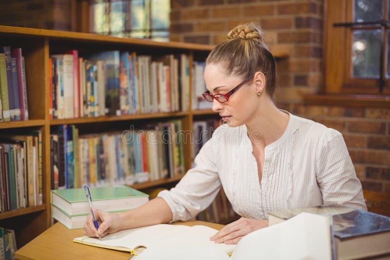 Professeur blond corrigeant dans la bibliothèque photo stock