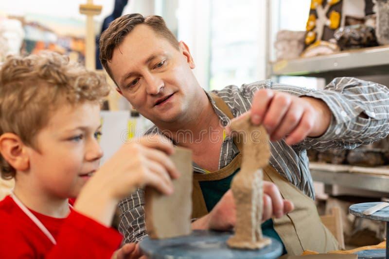 Professeur d'art aidant son ?tudiant sculptant des chiffres d'argile image stock