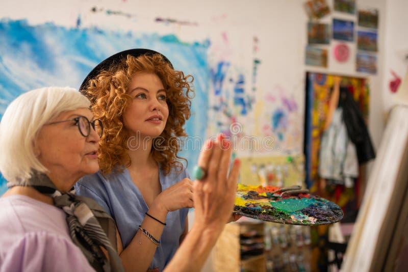 Professeur d'art dans le sentiment en verre satisfait du travail de son étudiant photo stock