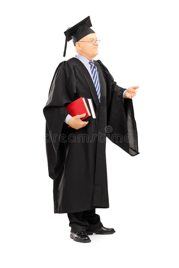 Professeur d'université dans la robe d'obtention du diplôme tenant des livres photographie stock libre de droits