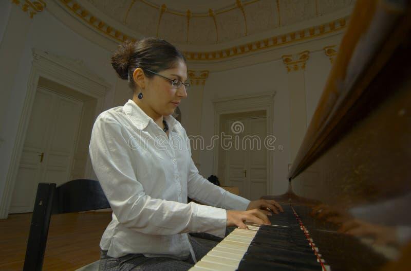 Professeur de piano jouant du point de vue de clavier images stock
