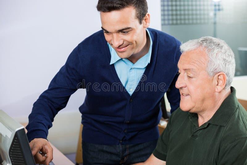 Professeur de sourire Assisting Senior Man en utilisant l'ordinateur images stock