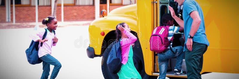 Professeur donnant la haute cinq aux enfants tout en entrant dans l'autobus photo libre de droits