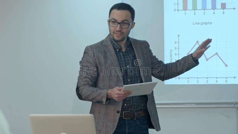 Professeur donnant la leçon aux étudiants à l'aide du comprimé numérique dans la salle de classe photo stock