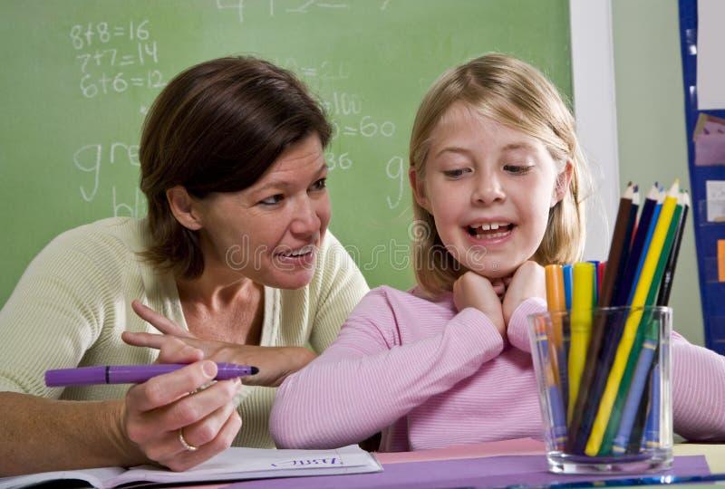 Professeur enseignant le jeune étudiant dans la salle de classe image libre de droits