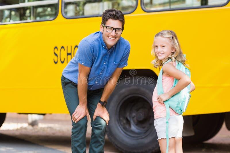 Professeur et écolière de sourire se tenant devant l'autobus scolaire image libre de droits