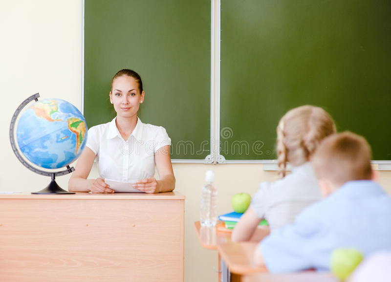 Professeur et écoliers dans la salle de classe à la leçon photographie stock libre de droits