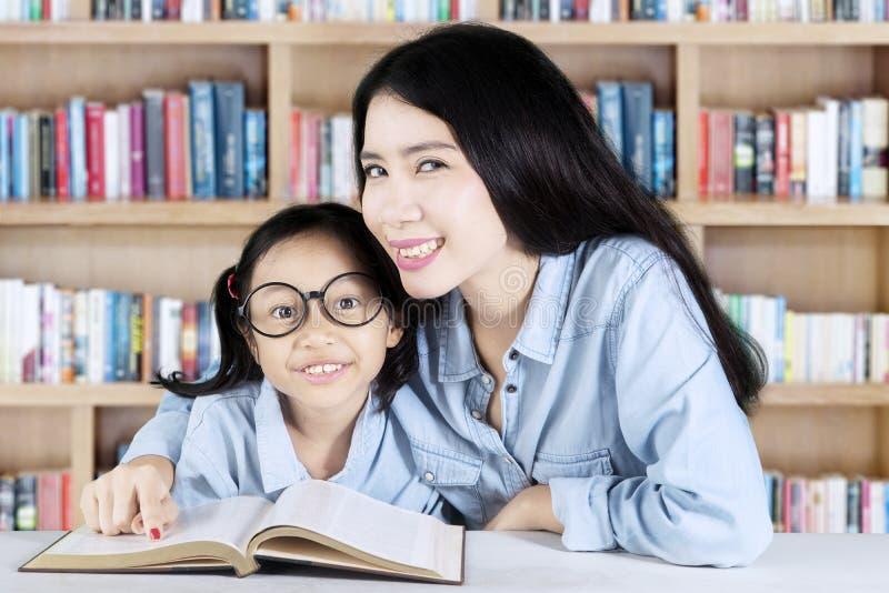 Professeur et étudiant apprenant ensemble dans la bibliothèque image stock
