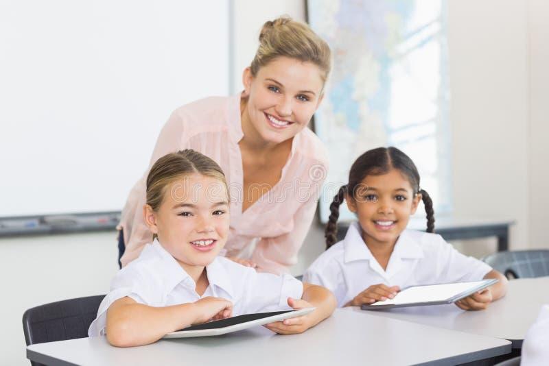 Professeur et enfants à l'aide du comprimé numérique photographie stock