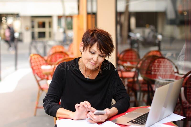 professeur féminin âgé travaillant en air ouvert avec l'ordinateur portable et le wri image stock