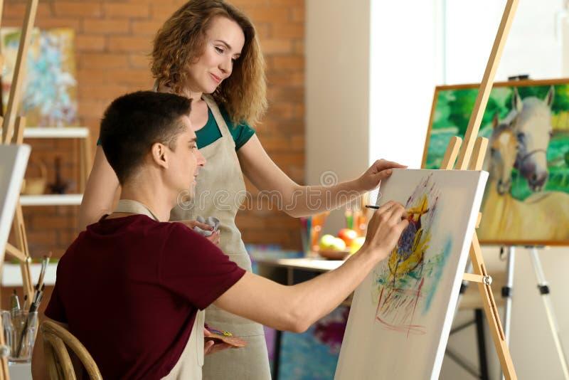 Professeur féminin aidant son étudiant pendant les classes à l'école des peintres photographie stock libre de droits
