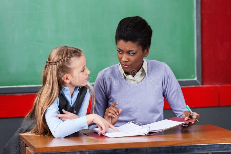 Professeur féminin Looking At Schoolgirl dans la salle de classe photos stock
