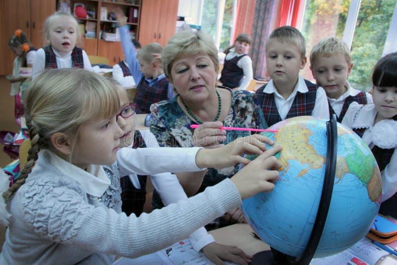 Professeur féminin montrant le globe aux enfants photos stock
