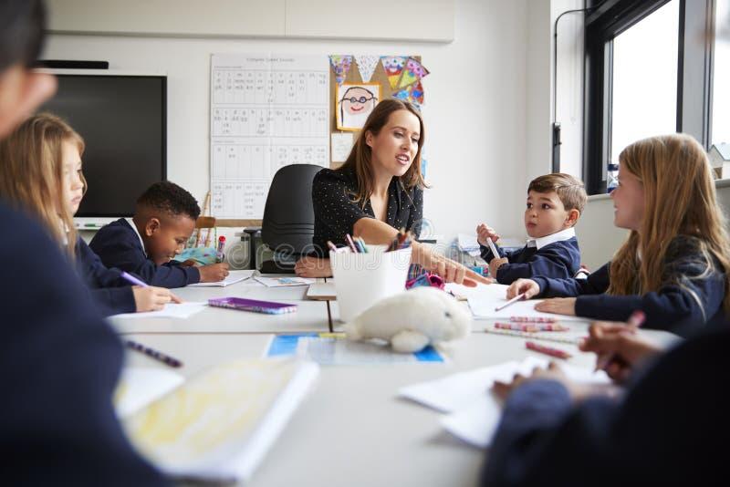 Professeur féminin s'asseyant à une table avec un groupe d'écoliers dans une leçon d'école primaire, angle faible, foyer sélectif photos stock
