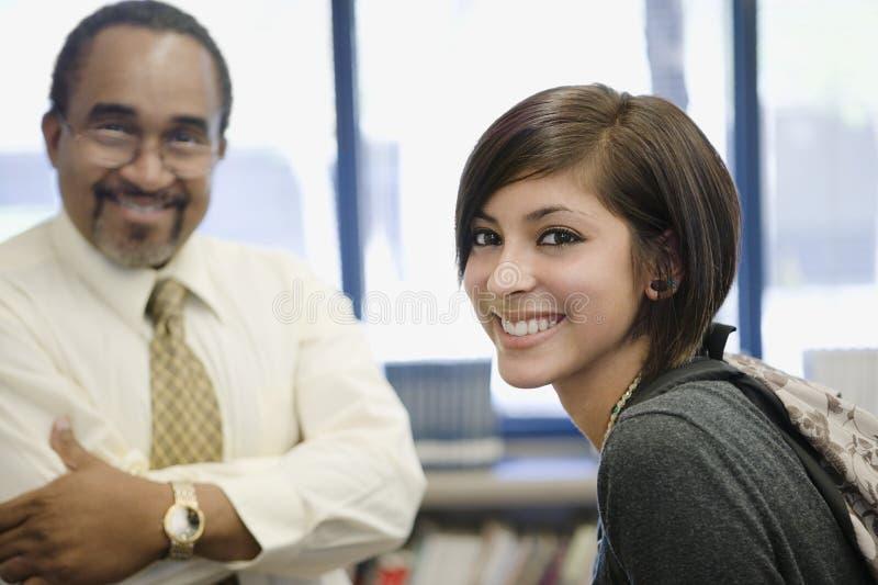 Professeur With Female Student dans la bibliothèque images stock