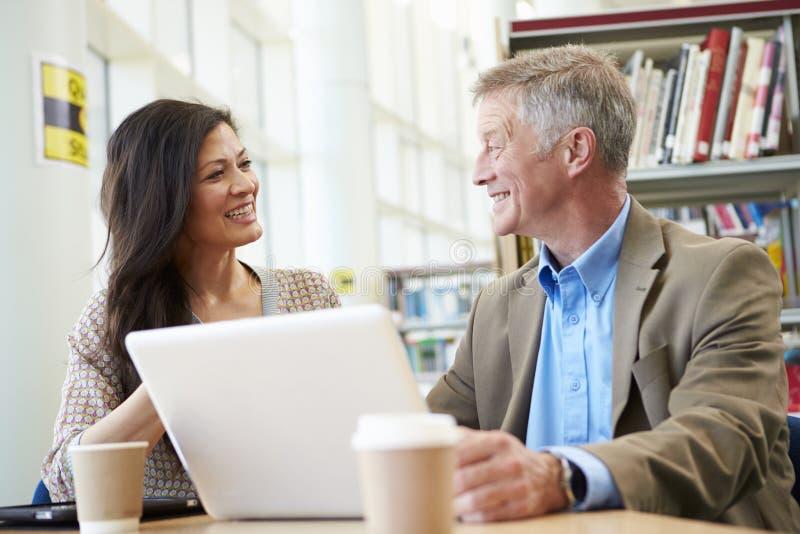 Professeur Helping Mature Student avec des études dans la bibliothèque photographie stock