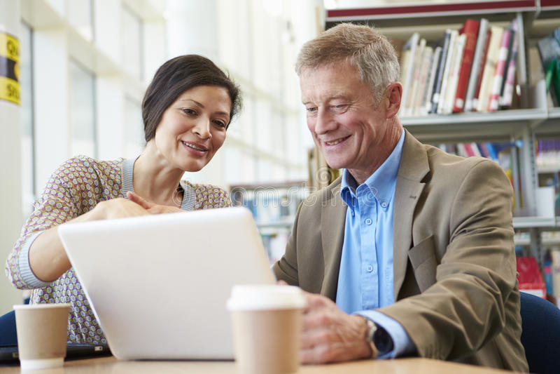 Professeur Helping Mature Student avec des études dans la bibliothèque photos stock