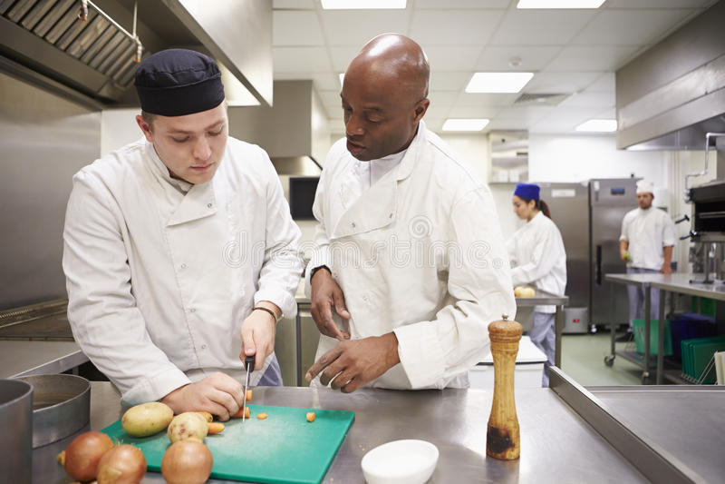 Professeur Helping Students Training à travailler dans la restauration photos stock