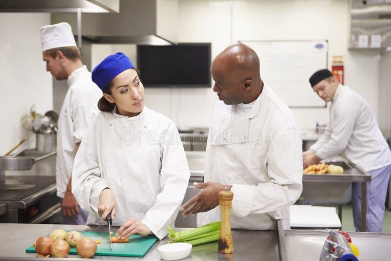 Professeur Helping Students Training à travailler dans la restauration images stock