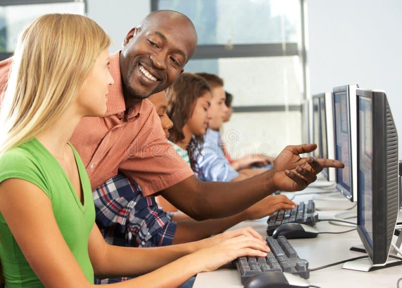 Professeur Helping Students Working aux ordinateurs dans la salle de classe photo stock