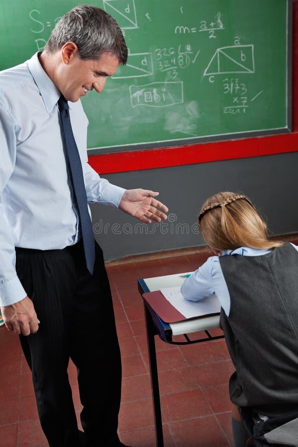 Professeur Looking At Schoolgirl dans la salle de classe photos stock