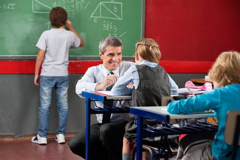 Professeur Looking At Schoolgirl tout en se tapissant à photos stock