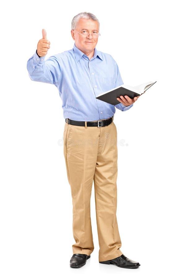 Professeur mâle retenant un livre et renonçant à un pouce images libres de droits