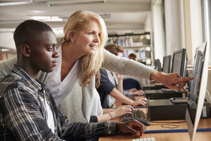 Professeur With Male Student travaillant sur l'ordinateur à la bibliothèque universitaire photographie stock libre de droits