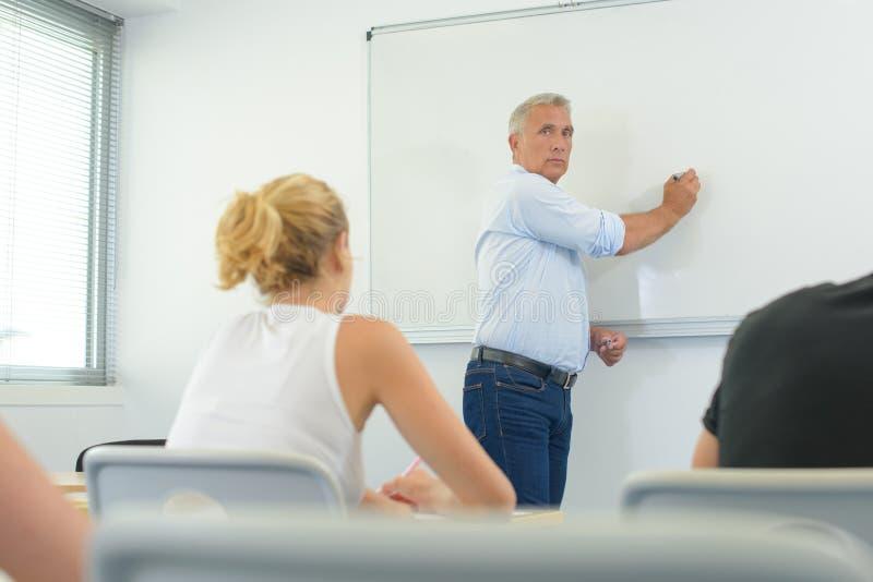 Professeur masculin écoutant des étudiants à la classe d'éducation des adultes image libre de droits
