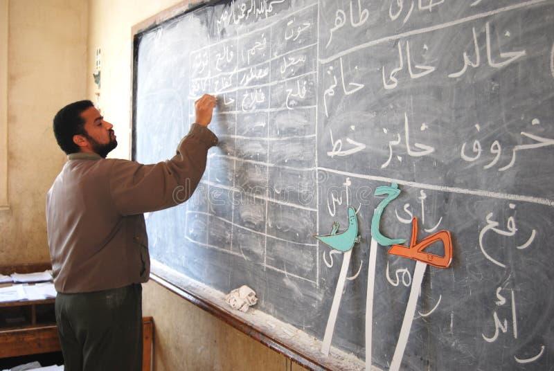 Professeur masculin dans la chambre de classe écrivant l'arabe sur le tableau noir image libre de droits