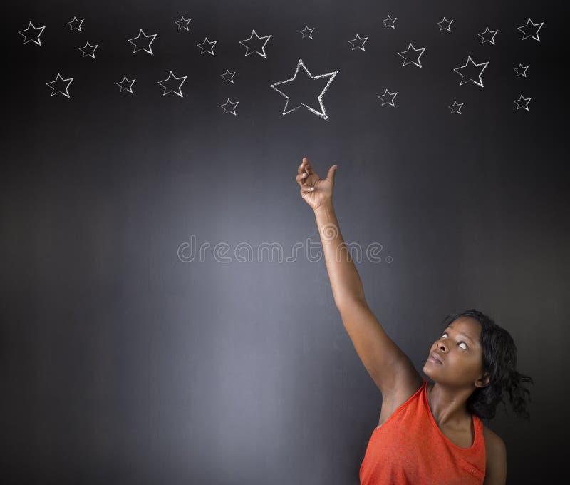 Professeur ou étudiant sud-africain ou d'Afro-américain de femme atteignant pour le succès d'étoiles photographie stock