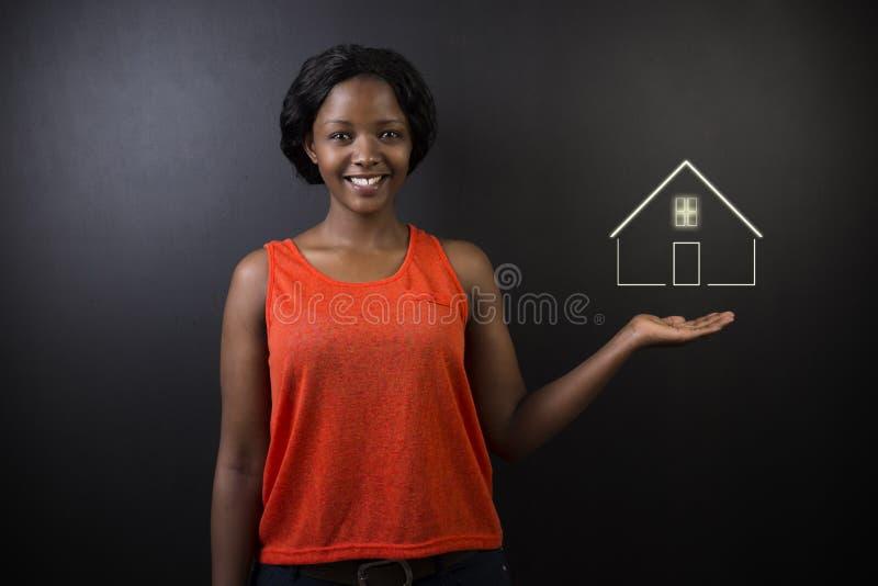 Professeur ou vendeuse sud-africain ou d'Afro-américain de femme sur le fond noir avec la maison à la maison ou les immobiliers photographie stock libre de droits
