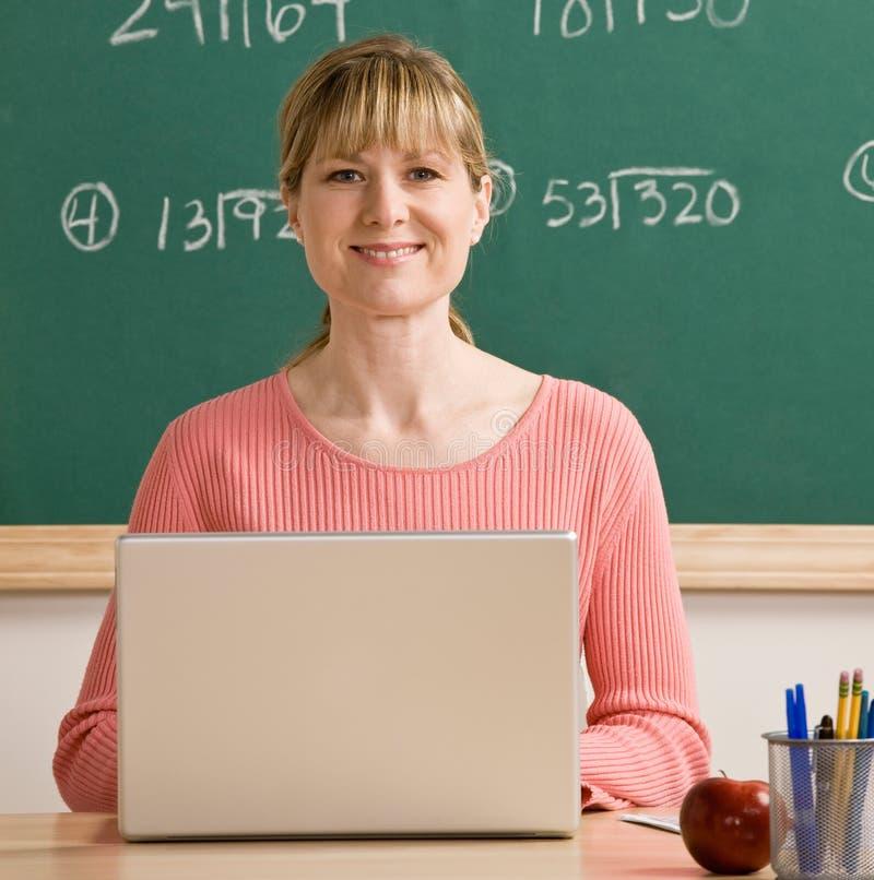 Professeur posant avec l'ordinateur portatif dans la salle de classe d'école photographie stock libre de droits