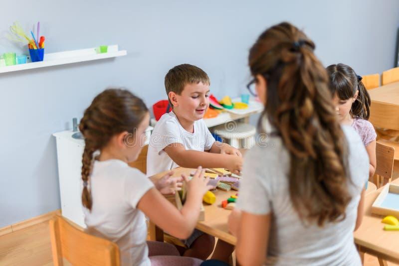Professeur préscolaire avec des enfants jouant avec les jouets didactiques colorés au jardin d'enfants images libres de droits