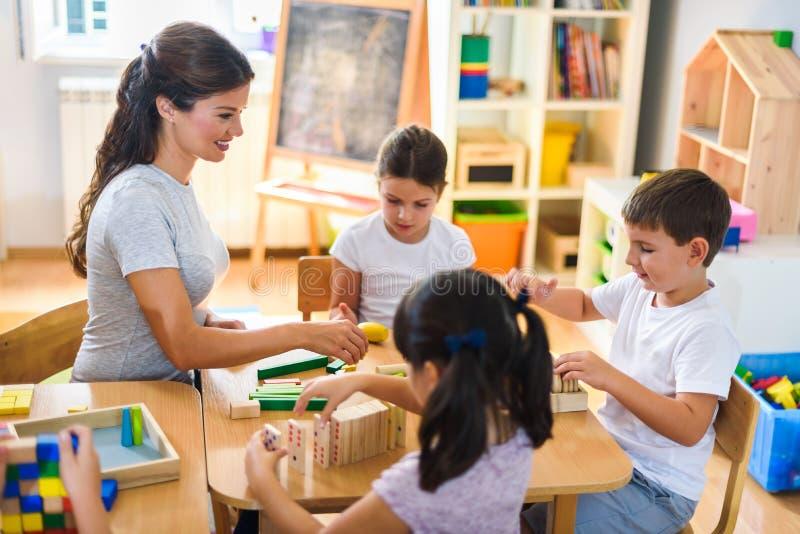 Professeur préscolaire avec des enfants jouant avec les jouets didactiques colorés au jardin d'enfants image stock