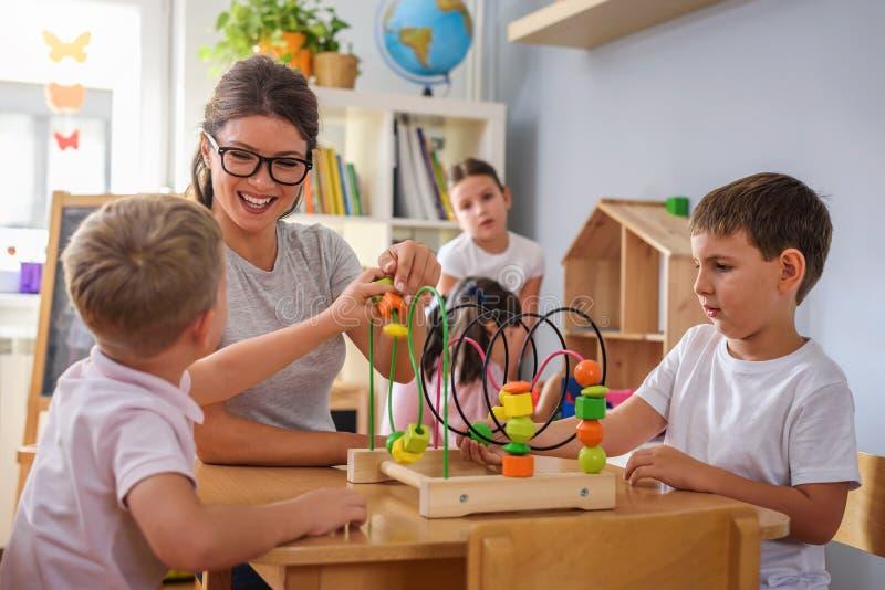 Professeur préscolaire avec des enfants jouant avec les jouets didactiques colorés au jardin d'enfants photographie stock
