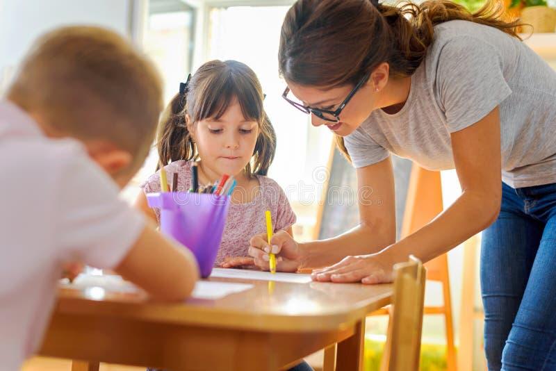 Professeur préscolaire regardant l'enfant futé apprenant à écrire et dessiner photographie stock