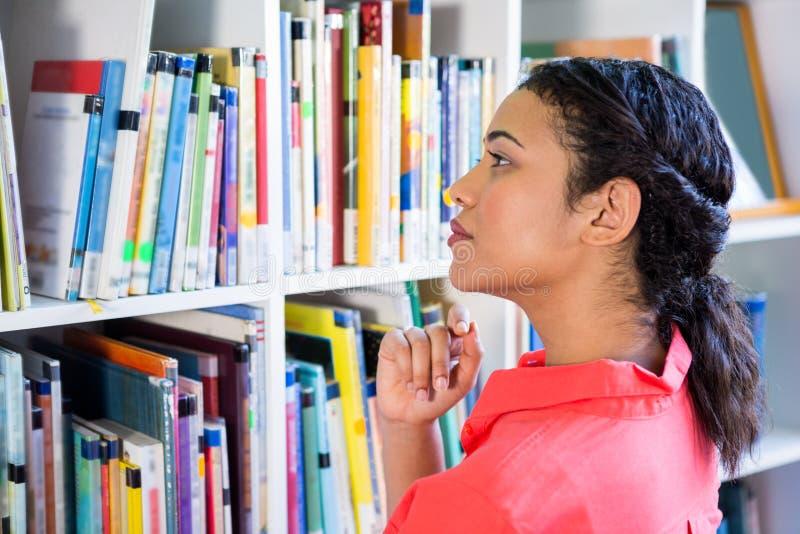 Professeur recherchant le livre dans la bibliothèque d'école images libres de droits