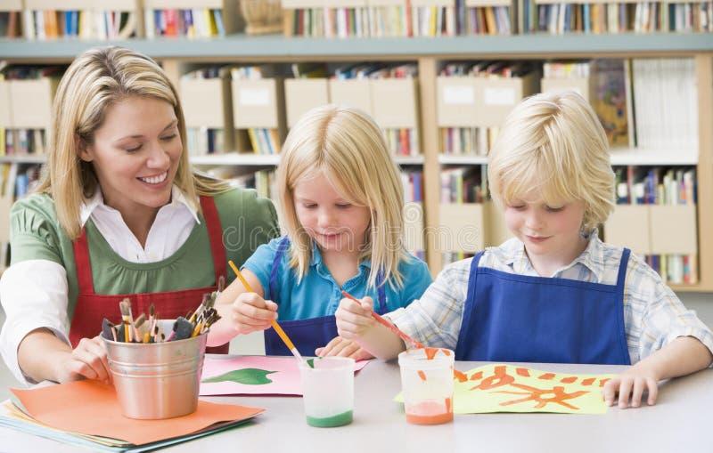 Professeur s'asseyant avec des étudiants dans la classe d'art image stock
